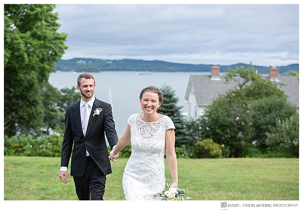 bride and groom holding hands, walking up a hill towards photographer during their elegant Castine Maine wedding day