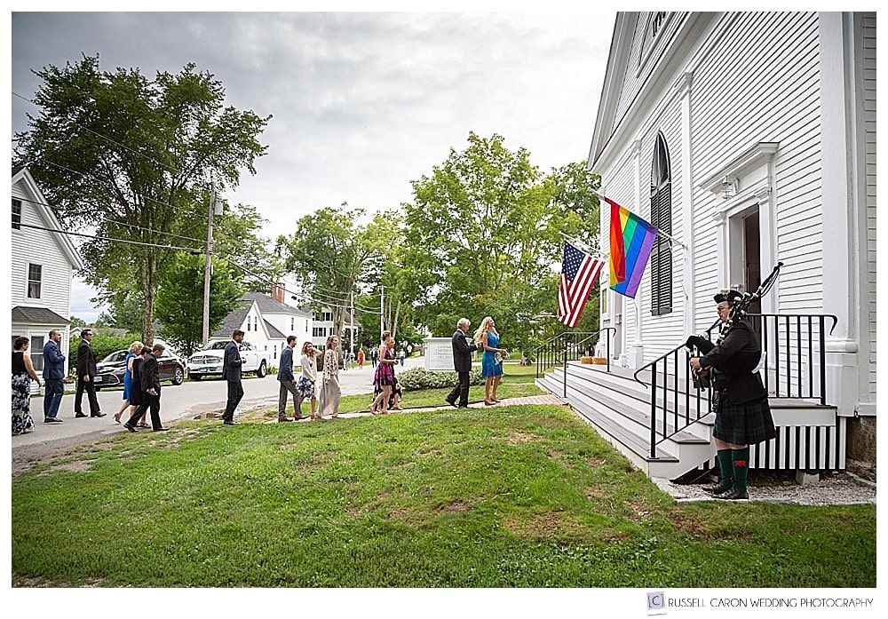 Guests entering the Castine, Maine, Unitarian Universalist Church, while a bagpiper plays outside