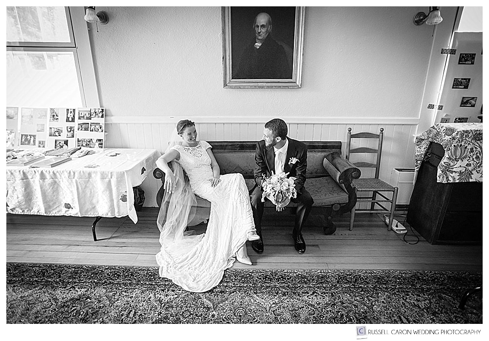 Black and white photo of a bride and groom relaxing in the UU Church of Castine, Maine