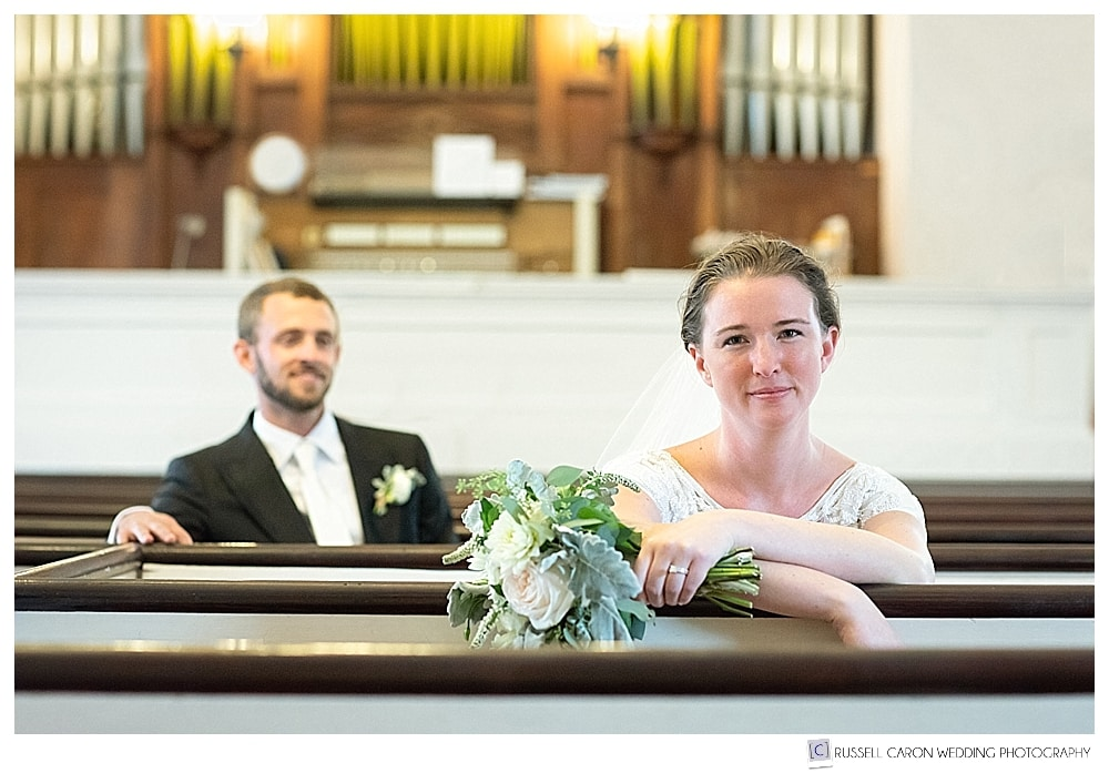 Bride and groom sitting in the pews of the UU Church, Castine, Maine