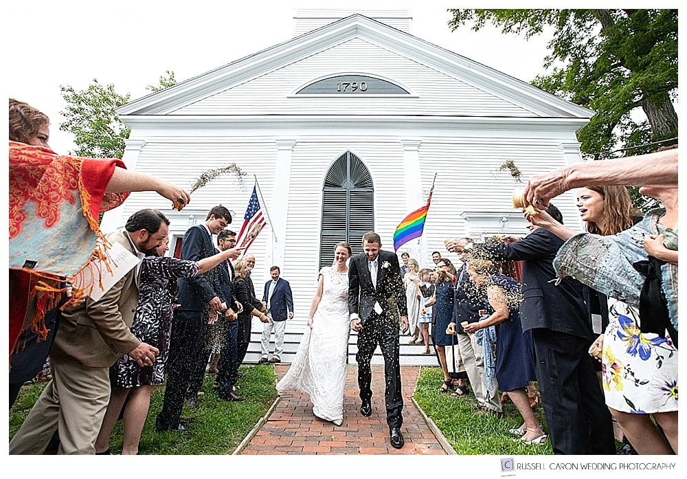 Bride and groom during recessional on the front steps of the UU Church, in Castine, Maine, while guests throw lavender buds