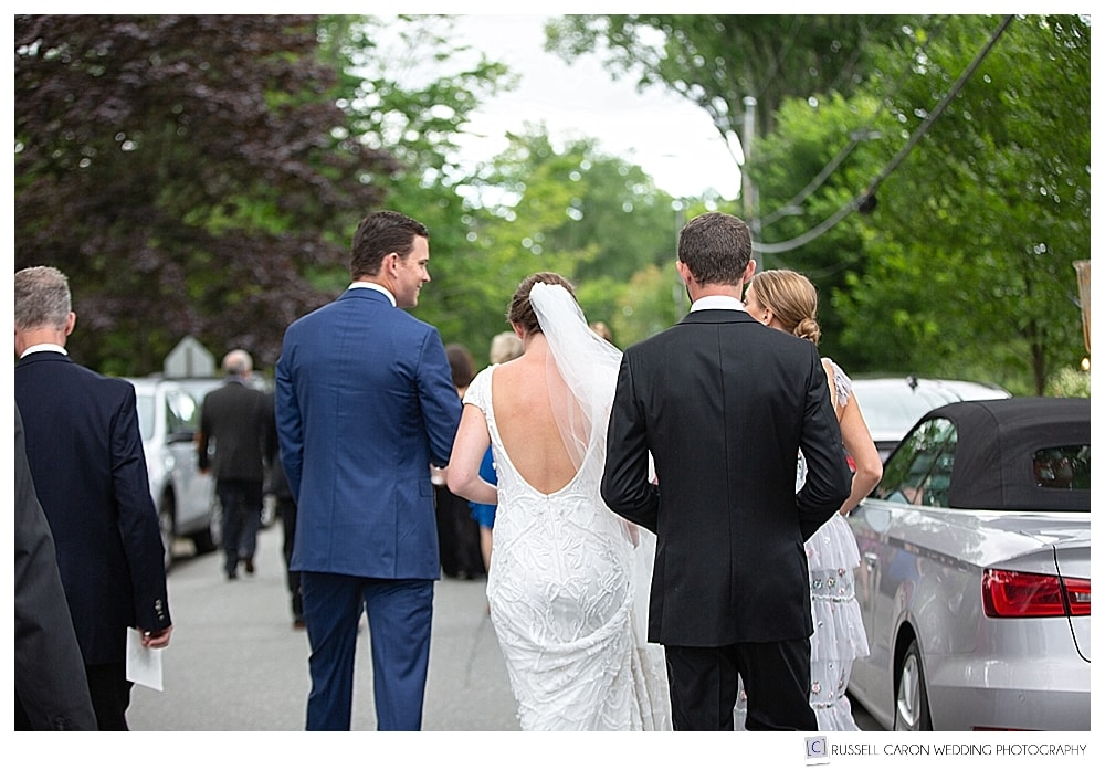 Bride and groom walk with guests down Court Street in Castine, Maine