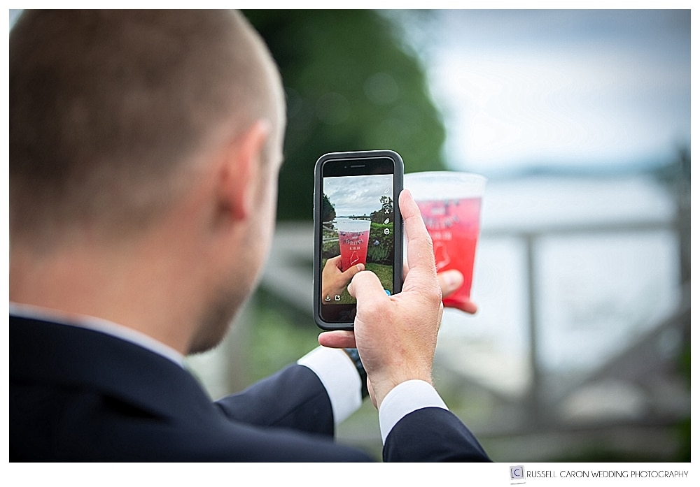 Man takes a photo of a red drink