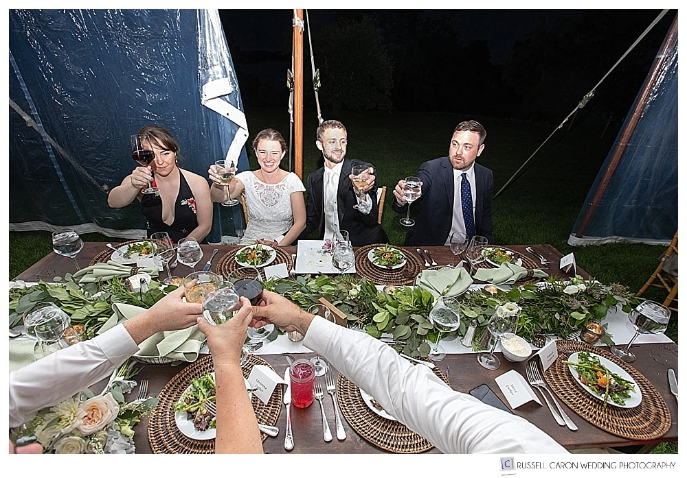 Bride and groom and friends, toasting to each other during a tented wedding reception in Castine, Maine