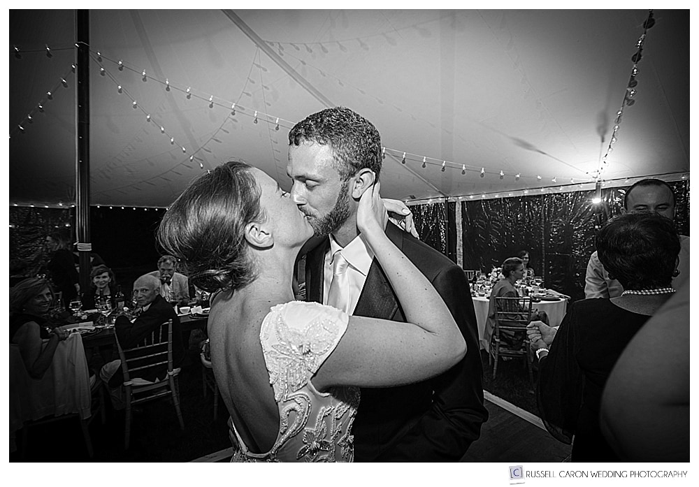 Bride and groom kissing on the dance floor of a tented wedding reception