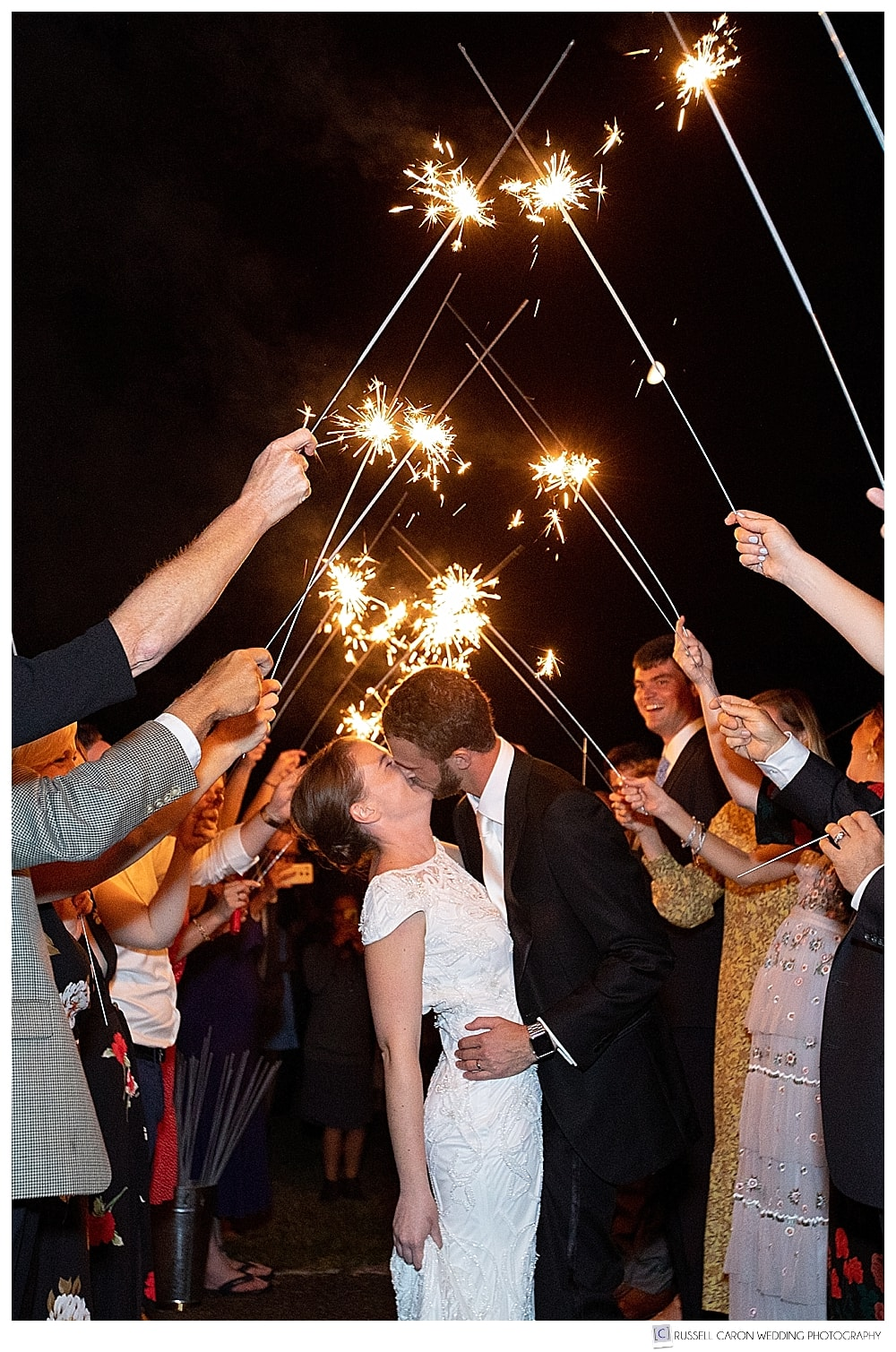 Bride and groom kissing under an arch of lit sparklers