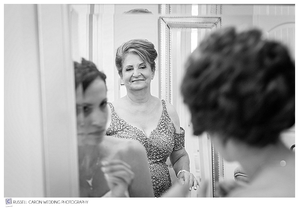 bride looking in mirror while getting ready