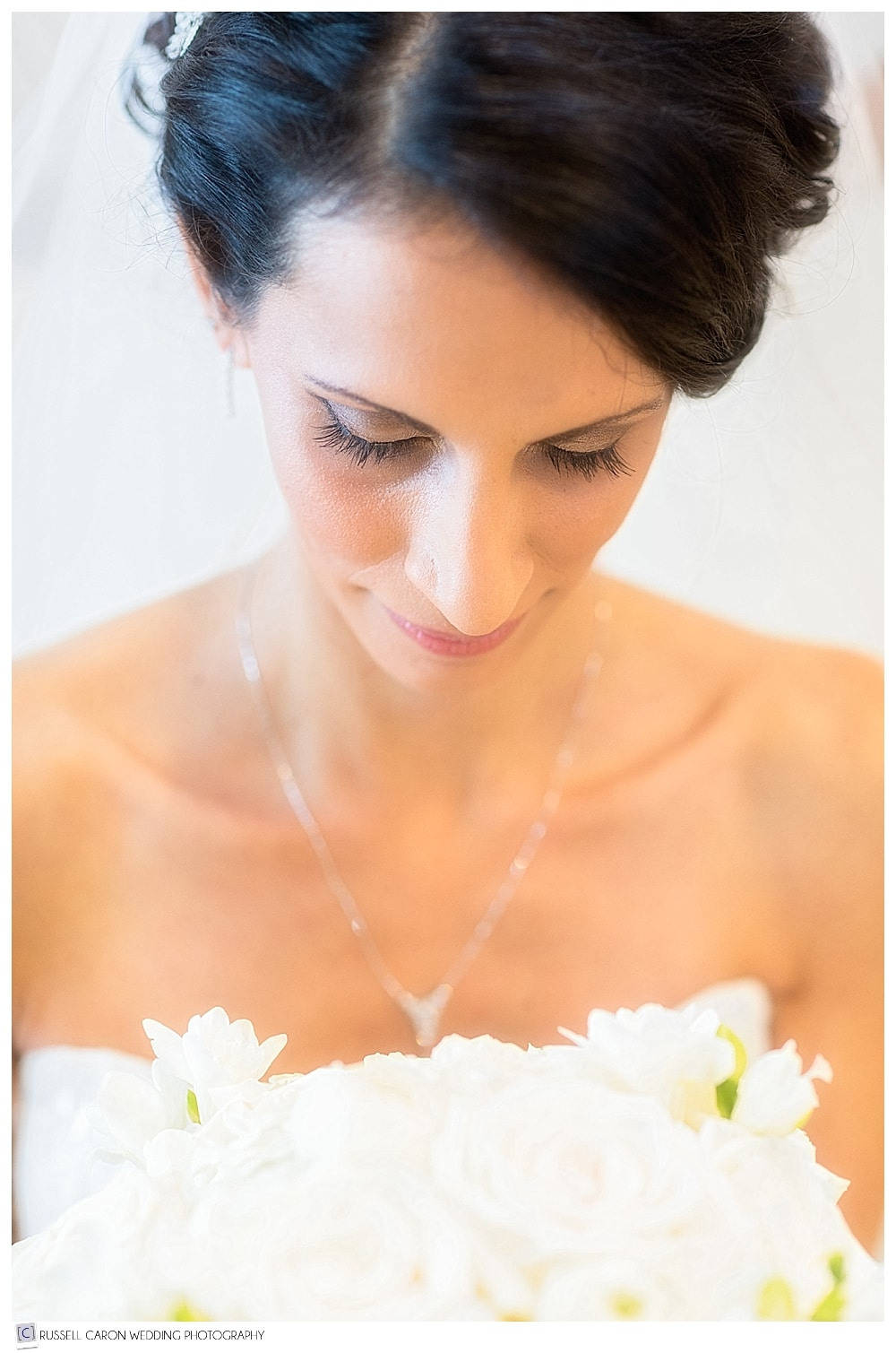 Portrait of bride looking down at bouquet