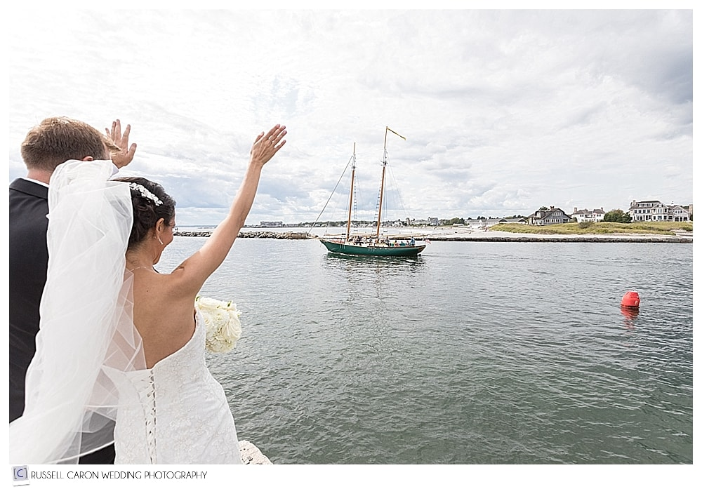 Bride and groom waving to sailboat in the Kennebunk River