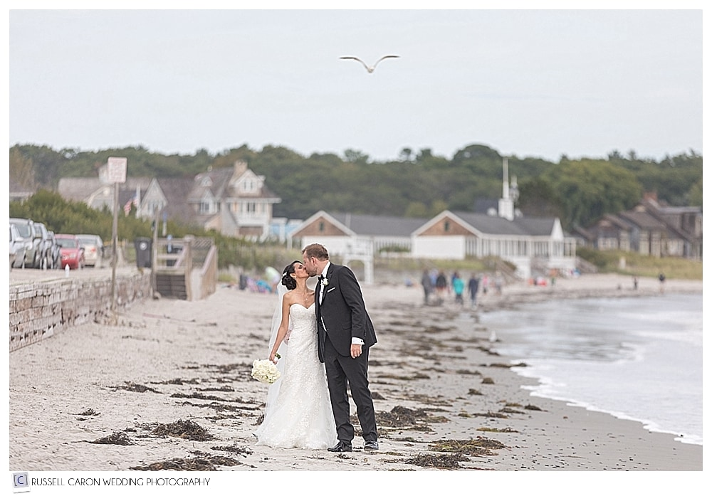 Bride and groom kissing on a Maine beach