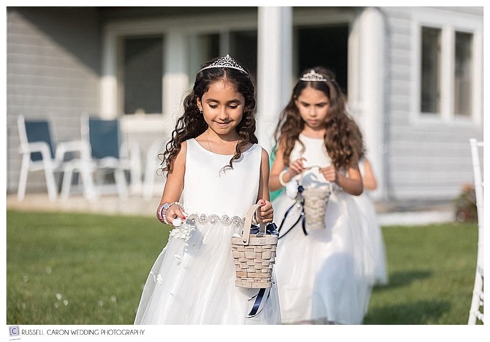 flower girls walking down the aisle during an outdoor wedding
