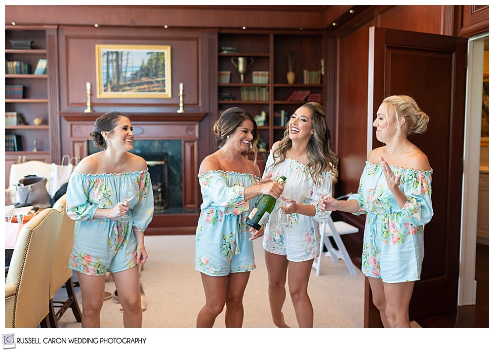 bride in white romper and three bridesmaids in mind rompers, opening a bottle of champagne and laughing