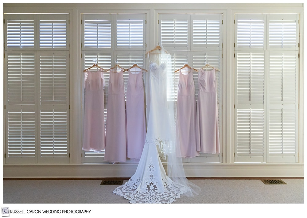 bride's white wedding dress hanging on levered shutters with the pink bridesmaid's dresses