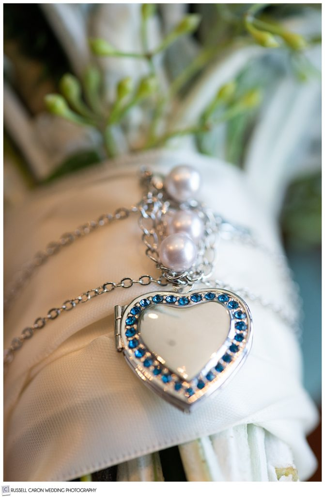 locket wrapped around the handle of a bridal bouquet
