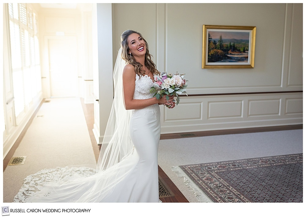 beautiful bride, fully dressed, holding her bouquet, smiling at the camera
