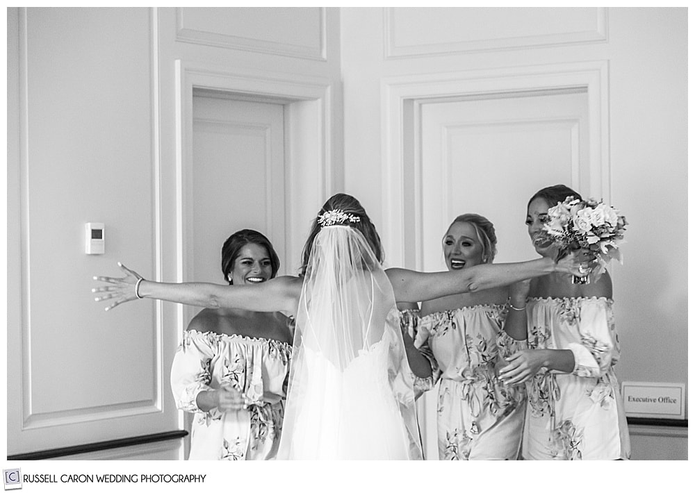 black and white photo of a bride, with her back to the camera, arms outstretched to hug her bridesmaids, who are smiling at her