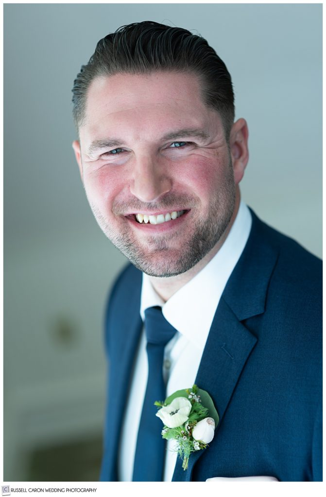 portrait of a smiling groom wearing a blue suit and tie