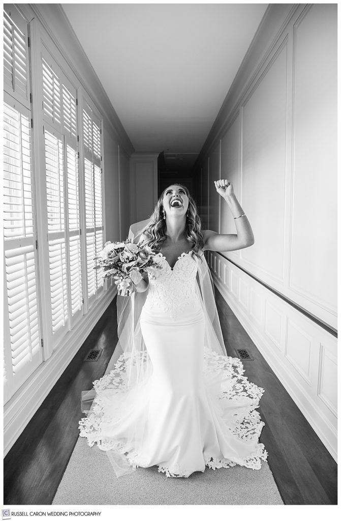 black and white photo of a bride dressed in a long white dress and veil, throwing her head back, and pumping her fist, in a hallway