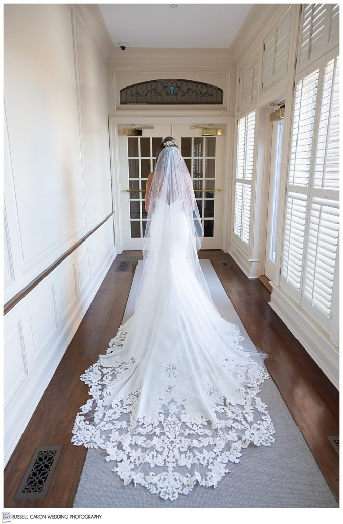 bride in a long white dress with lace edges, and long white veil in a hallway