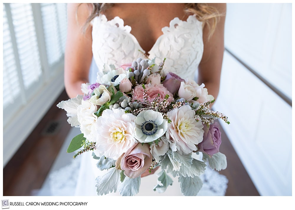 bride holding a beautiful bridal bouquet of pastel pink, yellow, lavender, and green bouquet from Seasons Downeast Designs