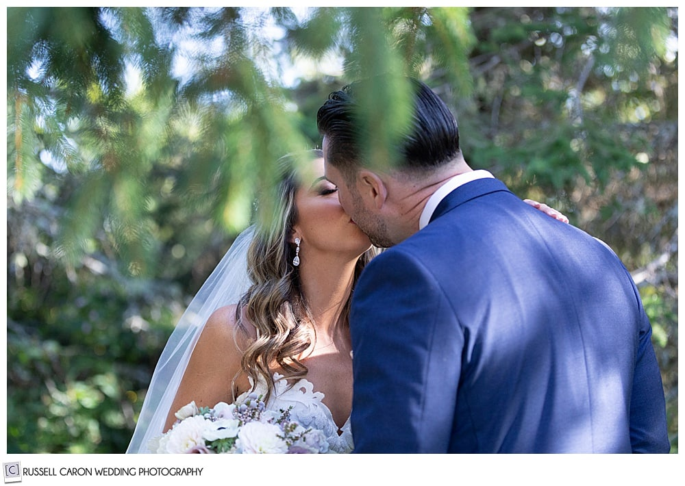 bride and groom kissing in a grove of trees during their first look photos