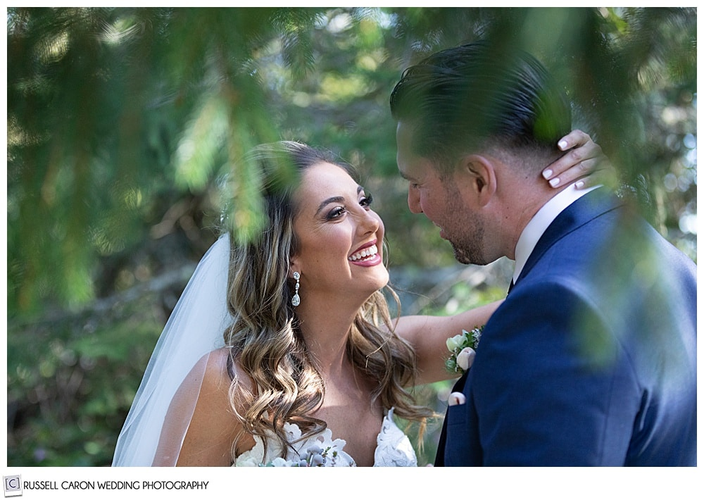 bride, her hand around the groom's neck, smiles during their first look in a grove of trees