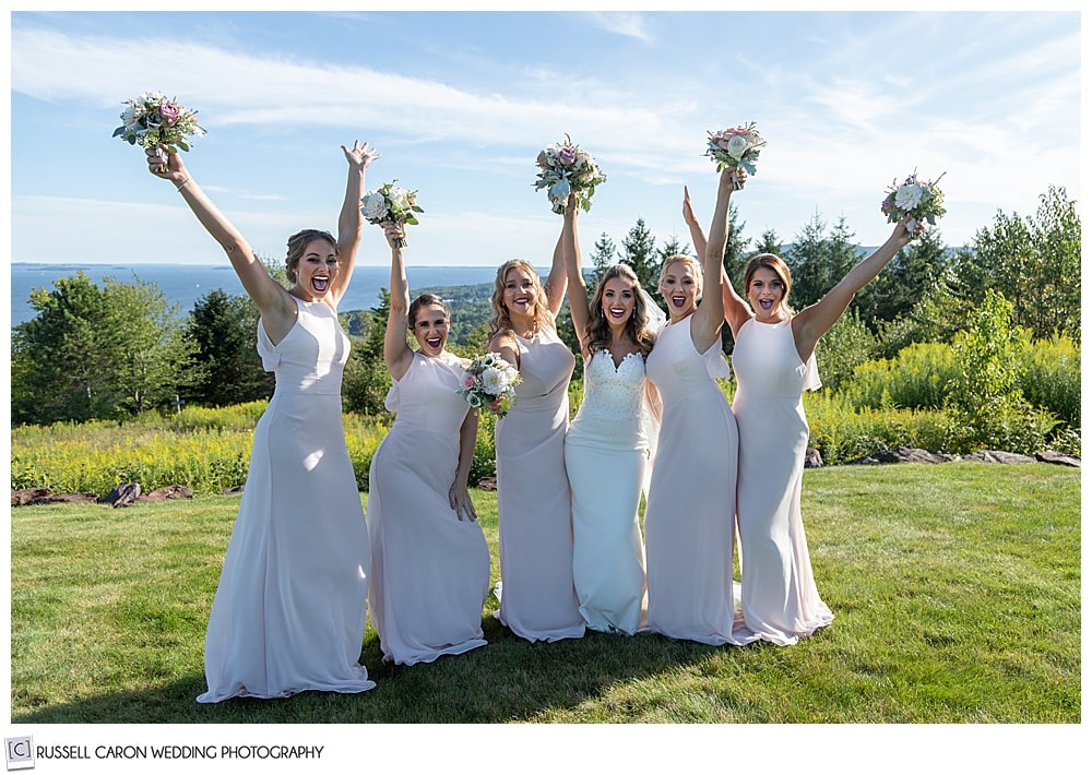 bride in white, whit five bridesmaids in pink, throwing their hands in the air and cheering