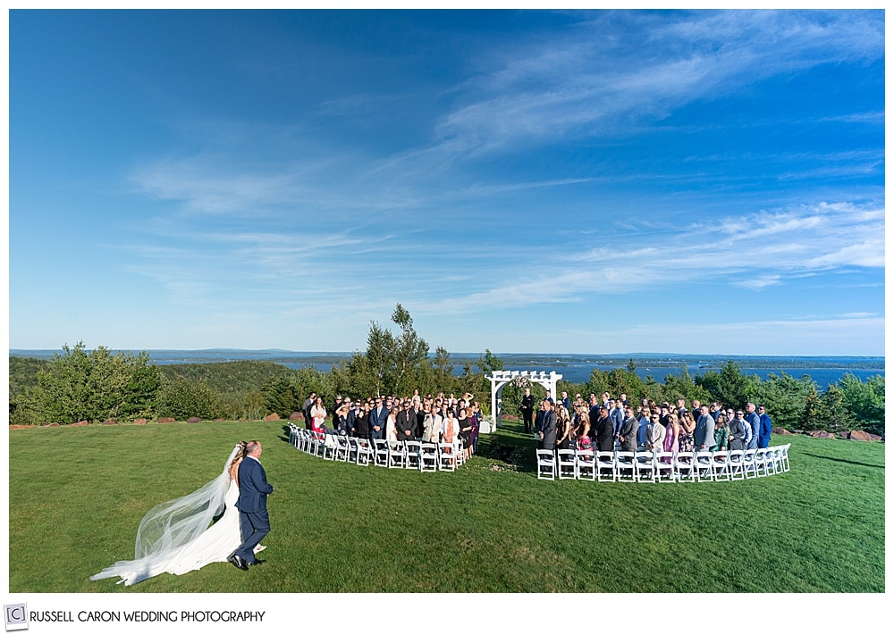 bride and her father approach the outdoor ceremony location at an elegant point lookout wedding