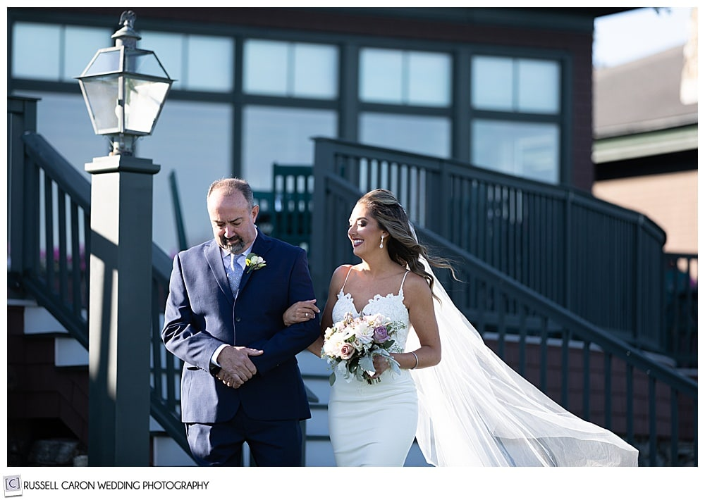 bride and her father coming down the steps as they approach the aisle at an elegant point lookout wedding ceremony