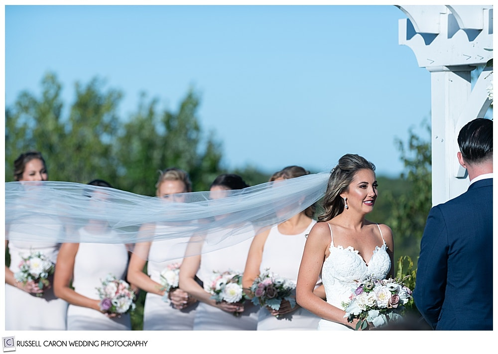 bride's veil blows during an elegant point lookout wedding ceremony outdoors