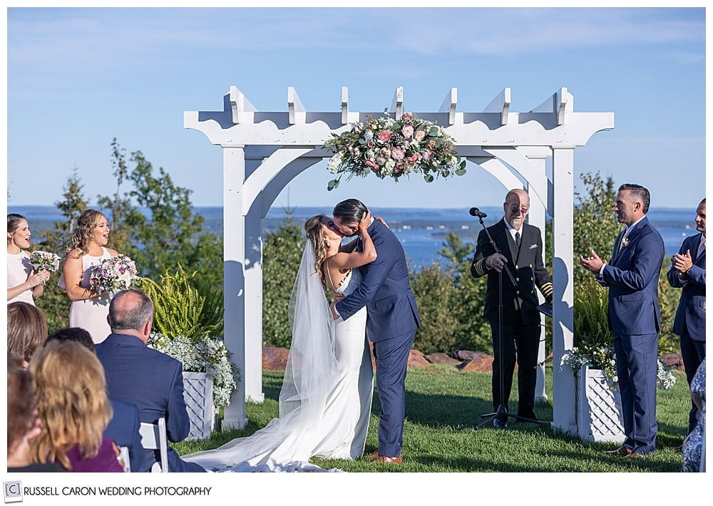 bride and groom during their first kiss at their elegant point lookout wedding ceremony, north port, Maine