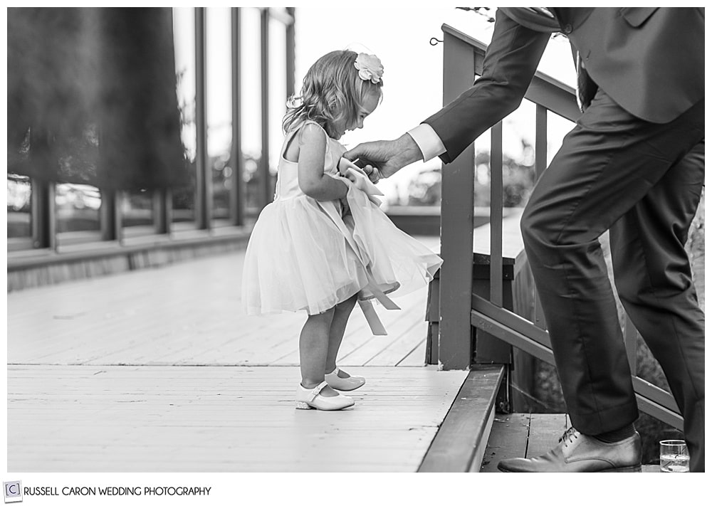 black and white photo of young girl near a stairway, with her father's arm coming in to help