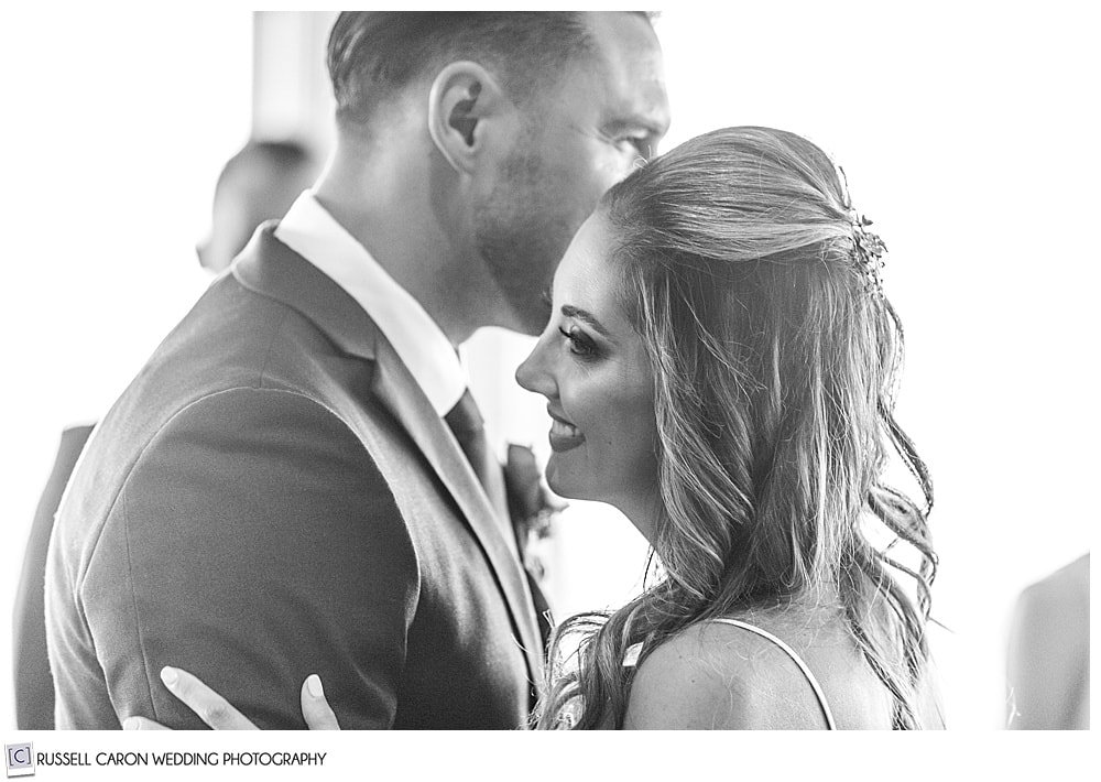 black and white photo of bride smiling during her first dance with her new husband