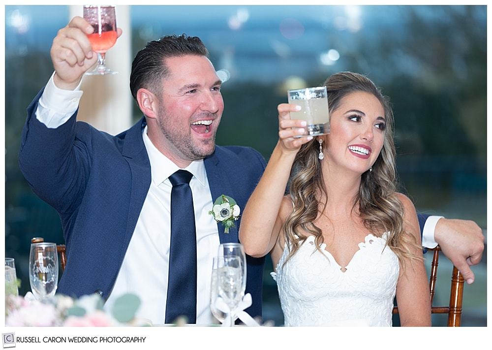 bride and groom, sitting next to one another, raising their glasses in a toast, and smiling