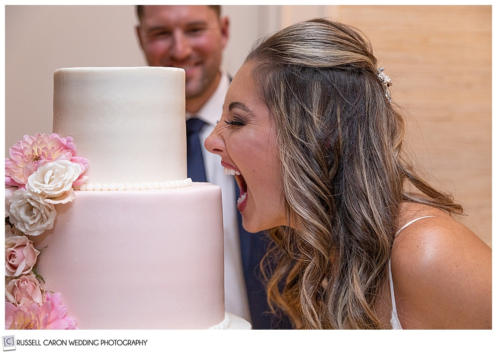 bride pretending to take a bite out of the entire wedding cake, groom is in the background smiling