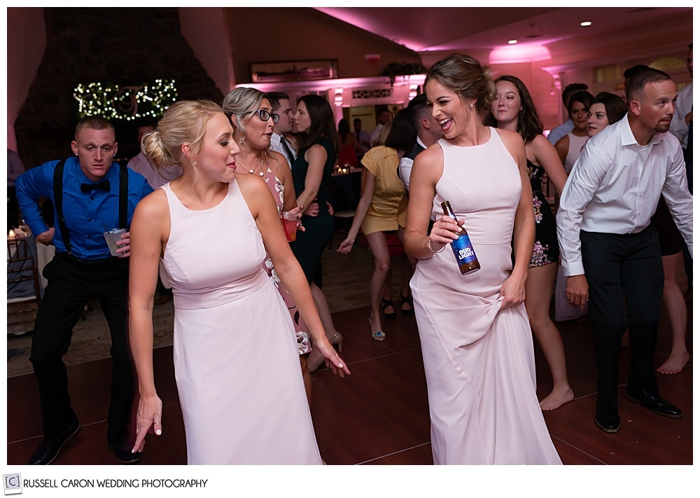 bridesmaids in pink, dancing at an elegant point lookout wedding in Maine