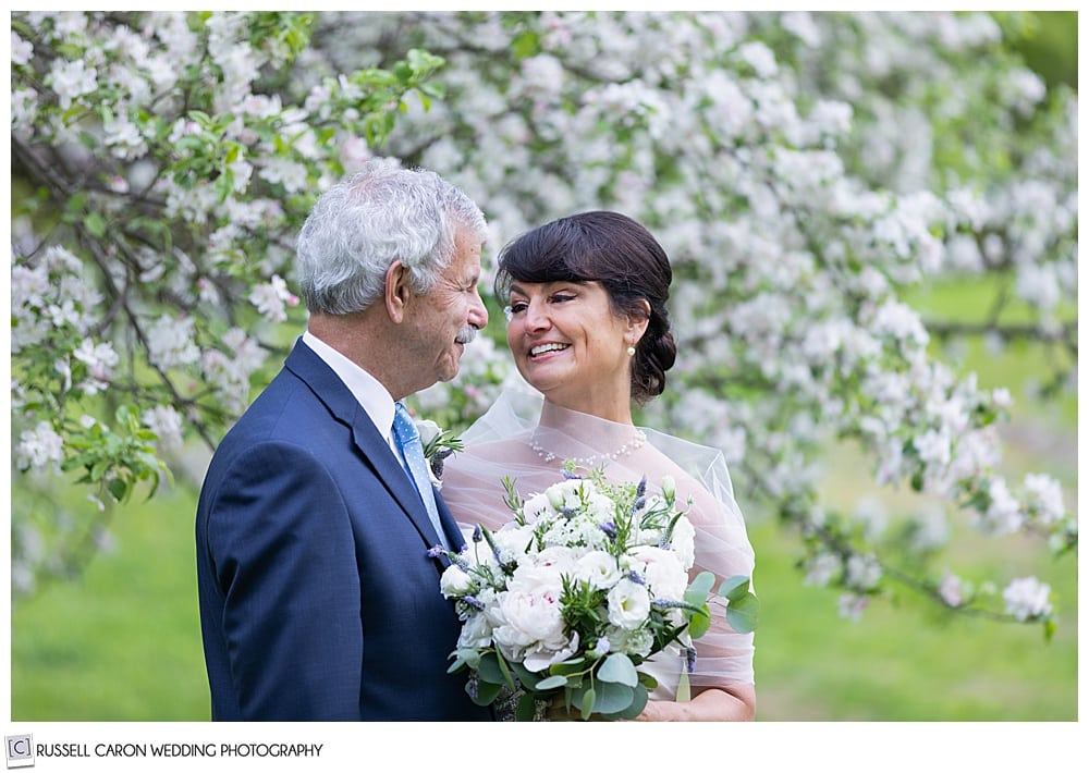 bride and groom smiling at each other amid apple blossoms
