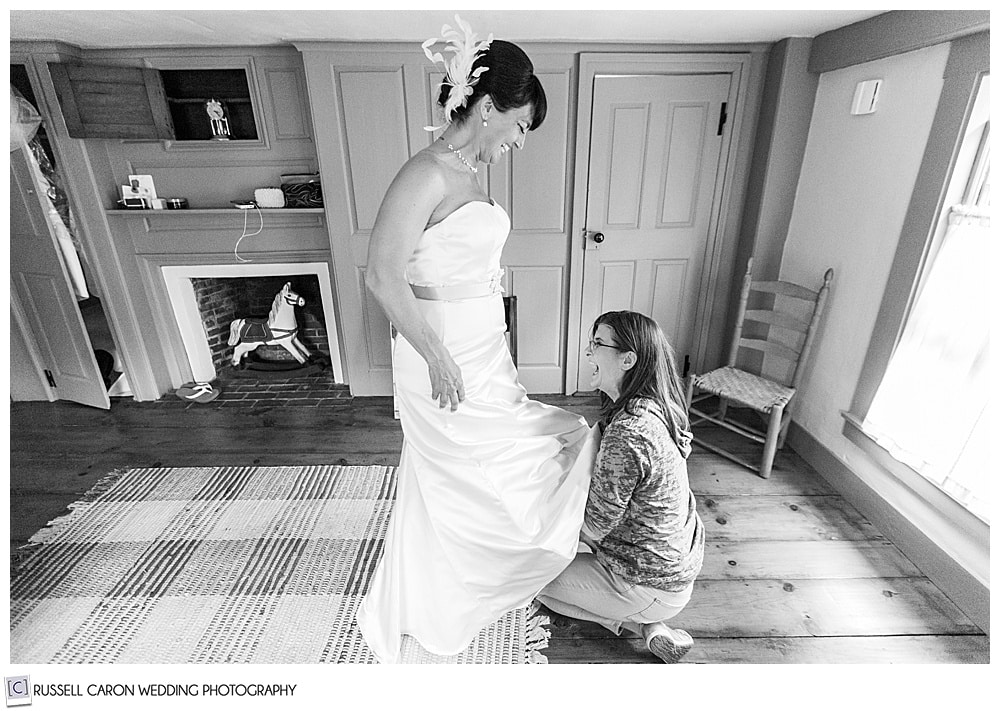 black and white photo of bride and matron of honor laughing
