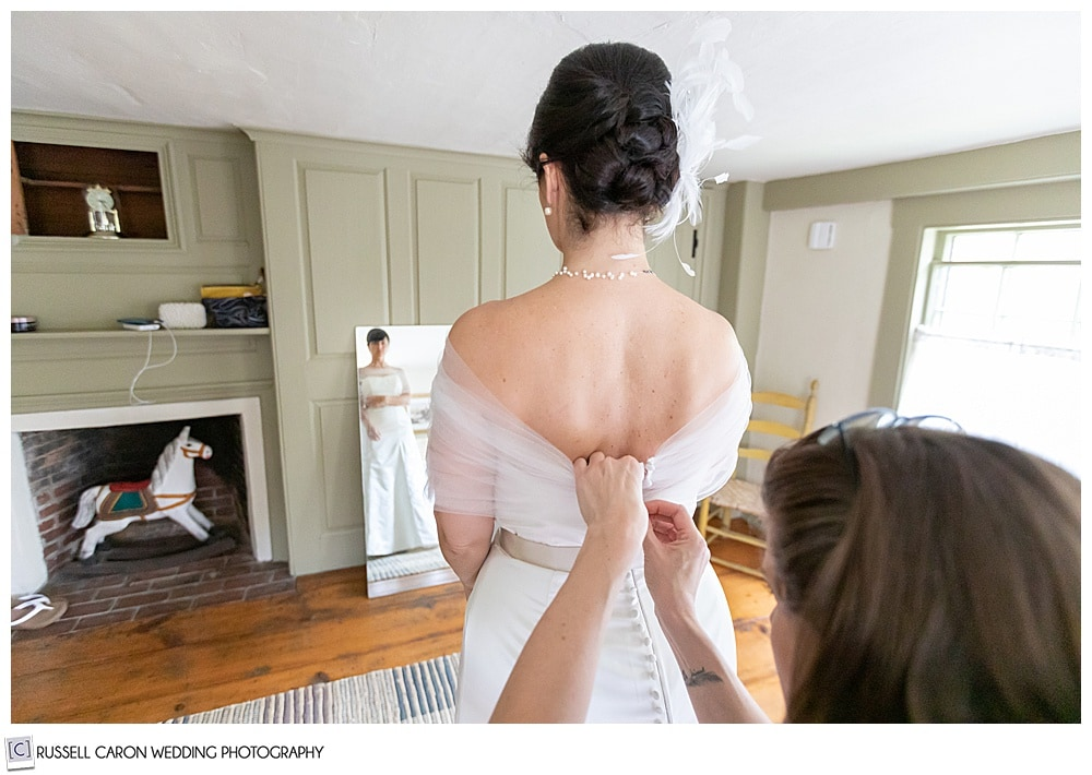 bride getting dressed with full length reflection in mirror
