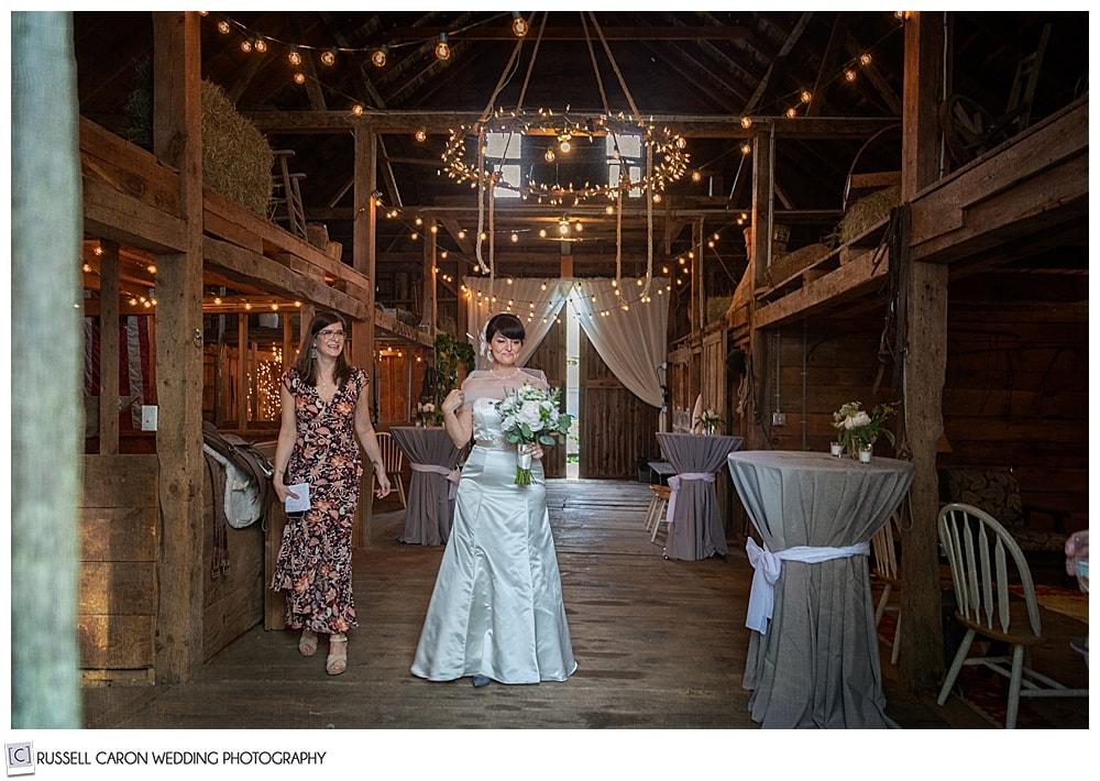 bride and maid of honor walk through wedding barn