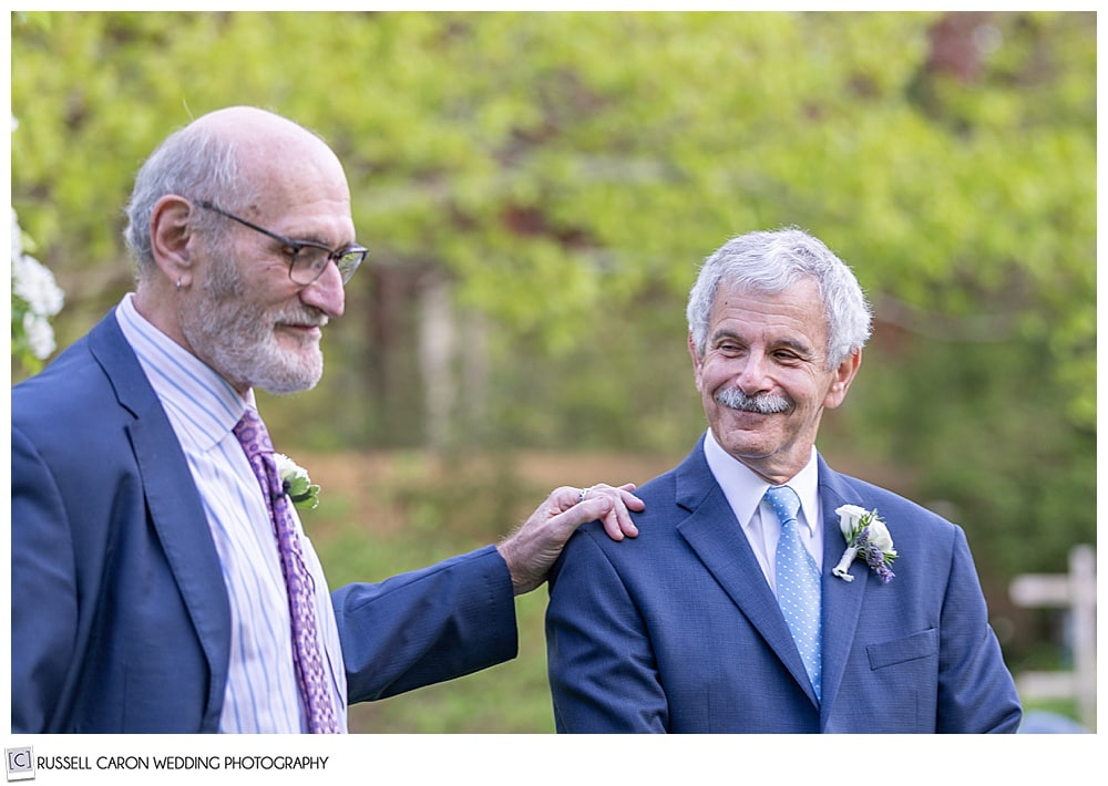 photo of the groom with his friend's hand on his shoulder