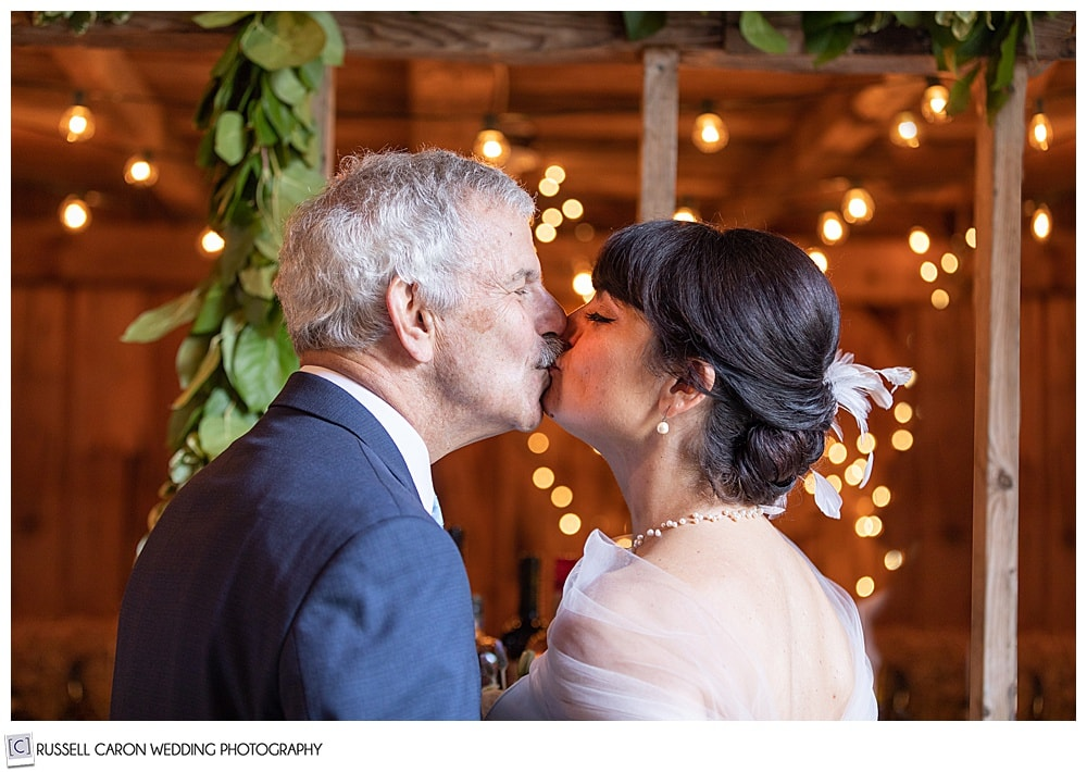 bride and groom kissing each other surrounded by lbokeh