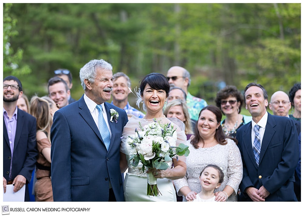 bride and groom laughing with friends and family