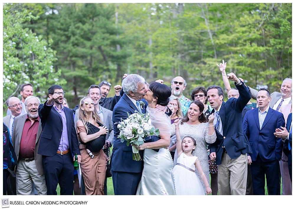 bride and groom kissing while surrounded by friends and family