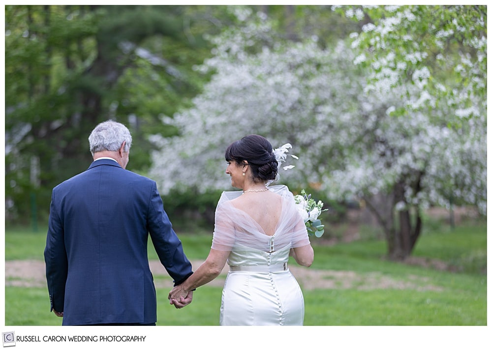 bride and groom holding hands and walking away in an apple orchard