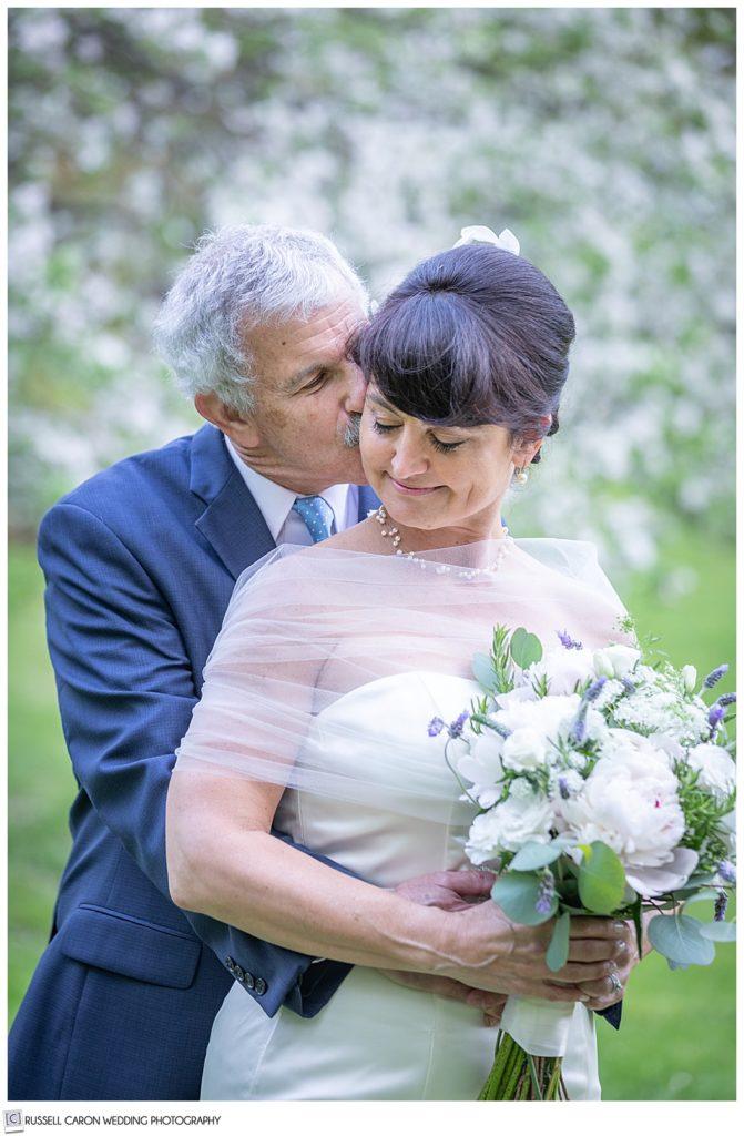 groom standing behind bride kissing her cheek