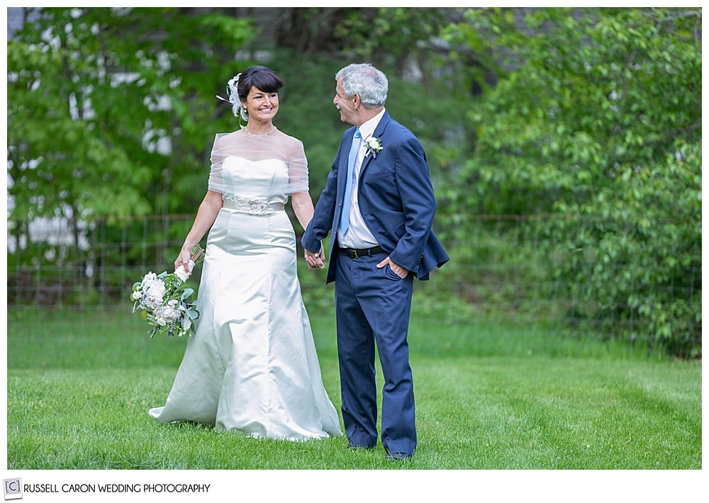 bride and groom holding hands and walking in a grassy field