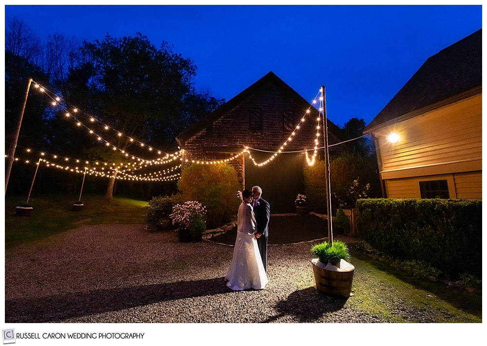 bride and groom standing in front of a barn with twinkly lights in the dark