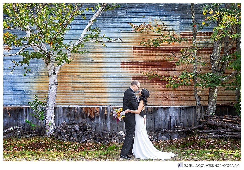 bride and groom in front of barn and birch tree