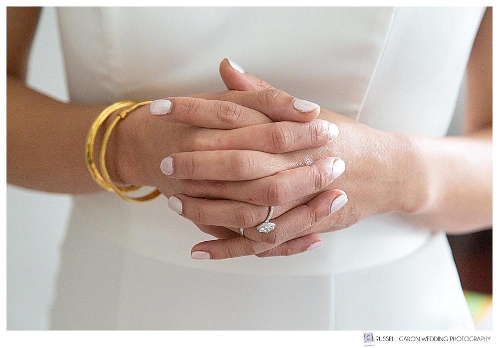 bride's clasped hands, wearing gold bracelets